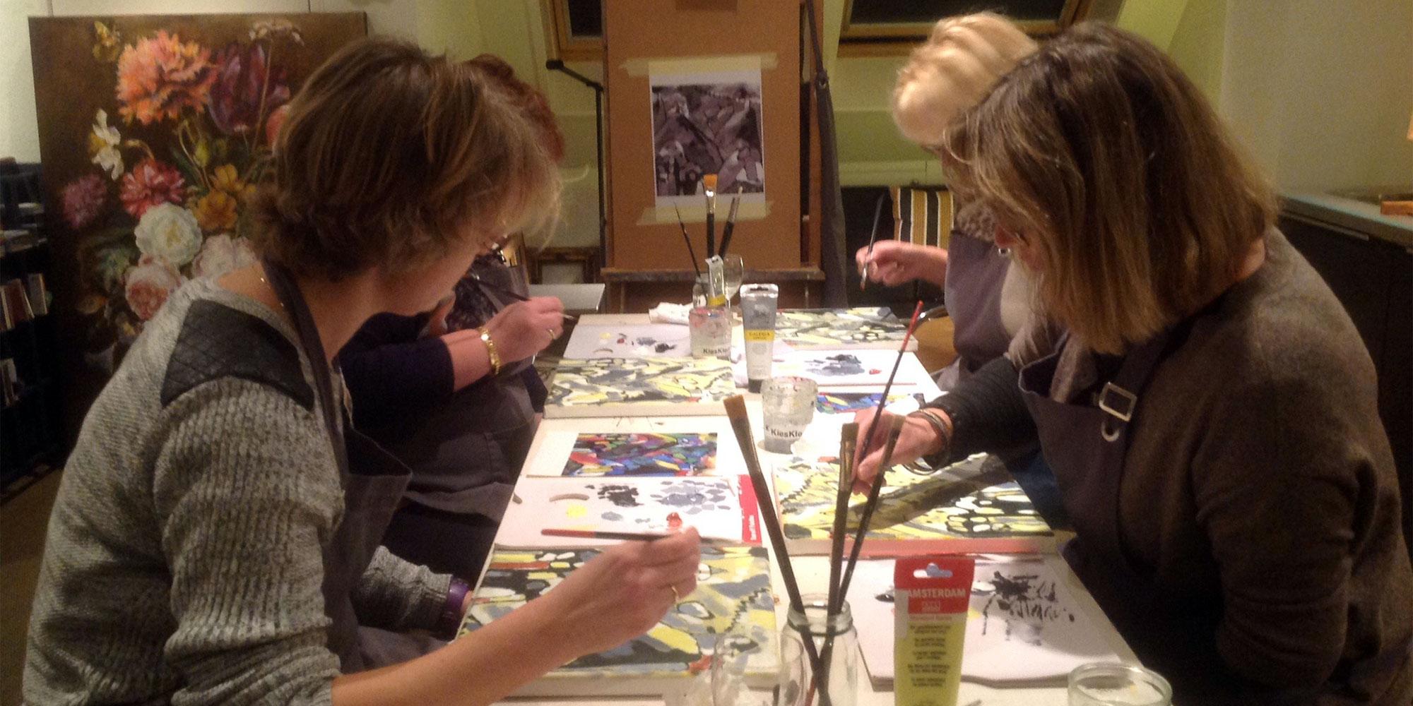 vier vrouwen schilderen in atelier