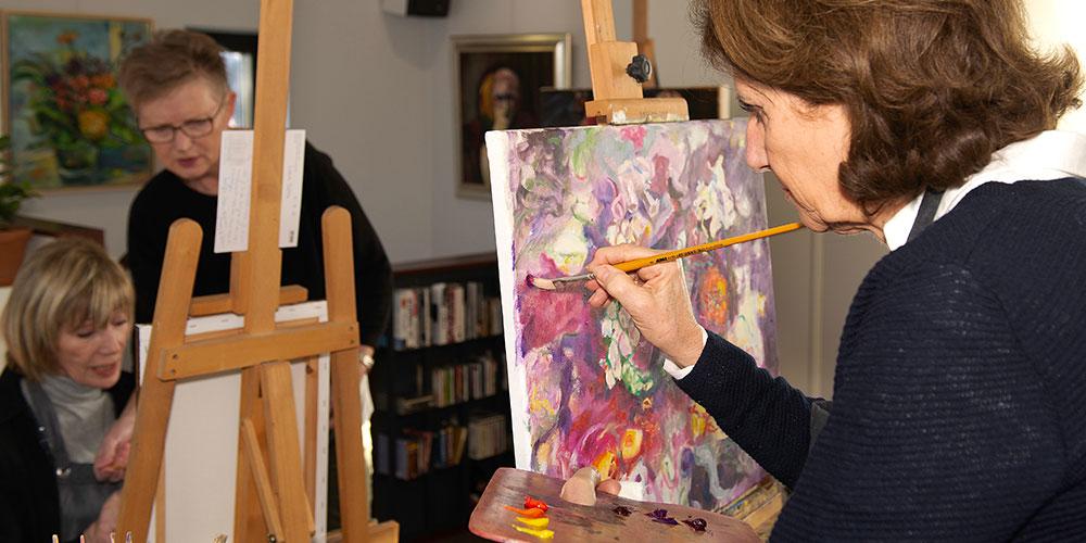 schilderles KiesKleur twee vrouwen schilderen op doeken, docent kijkt