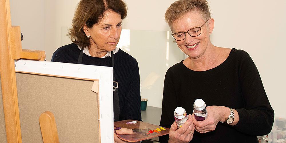 schilderles KiesKleur cursist en docent met twee tubes verf